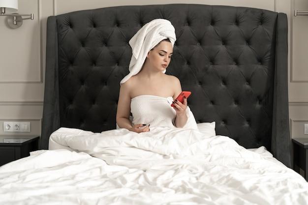 Привлекательная молодая кавказская девушка, завернутая в банное полотенце, с помощью смартфона, держа белую чашку, оставаясь в постели