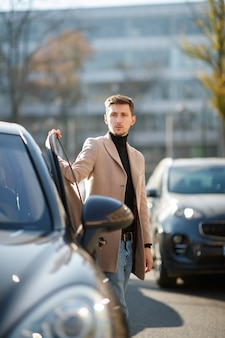 Привлекательный молодой кавказский человек открывает автомобильную дверь, одетую в бежевое пальто в центре города в солнечный день