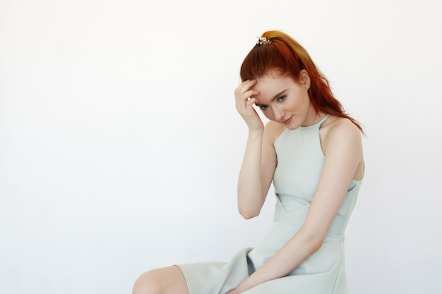 Attractive young caucasian redhead female looking away with shy smile. headshot of attractive charming young female student having timid cute look. youth and beauty concept
