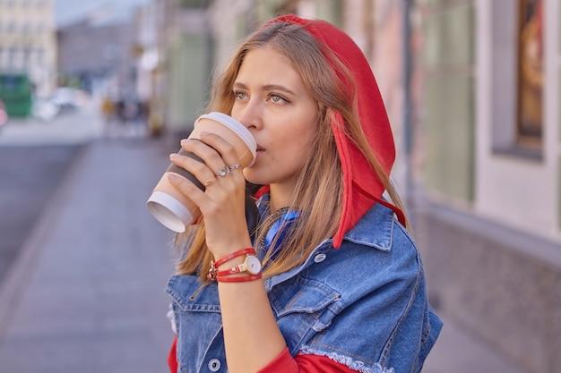 긴 금발 머리와 빨간 까마귀와 데님 재킷을 입은 약 25 세의 매력적인 젊은 백인 여성이 도심을 걷는 동안 종이 컵에서 커피를 마시고 있습니다.