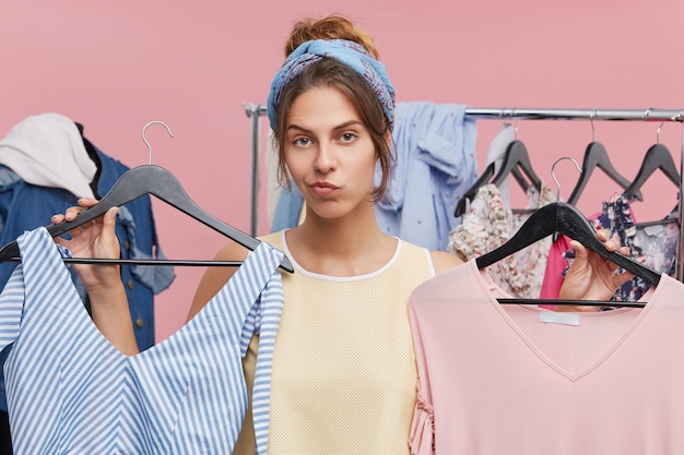 매력적인 젊은 백인 여자 고객 옷 두 조각으로 옷걸이 들고 어떤 수학 및 그녀에 맞는 결정하는 동안 의심 느낌. 쇼핑, 선택, 딜레마, 구매 및 구매