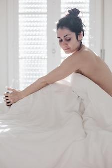 매력적인 젊은 백인 여성은 아침 시간에 침대에서 편안하게 휴식을 취하며 침실에서 신선한 부드러운 침구 린넨과 매트리스를 즐깁니다.