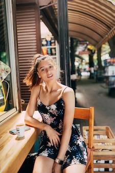Привлекательная молодая кавказская женщина, сидящая в уличном кафе