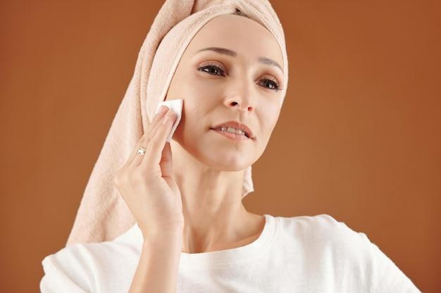 Привлекательная молодая кавказская женщина с полотенцем на волосах, снимая макияж с хлопковой салфетки на коричневом фоне