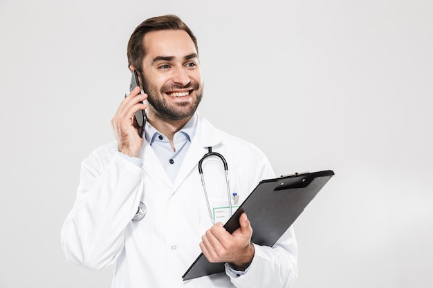 Attractive young cheerful male doctor wearing unifrom standing isolated over white wall, taking notes while talking on mobile phone