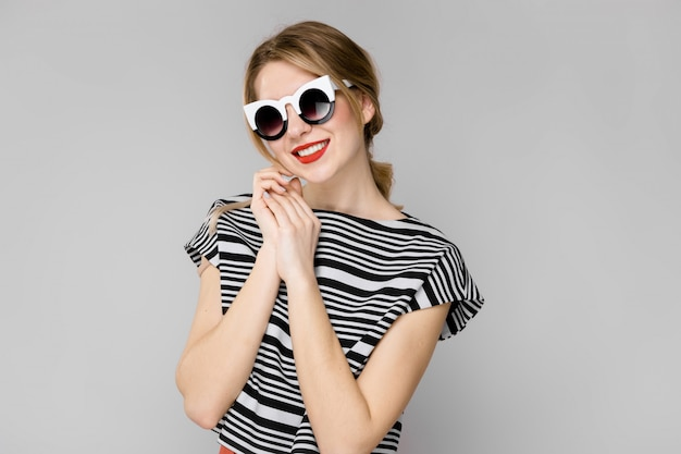 Attractive young confident blonde girl in striped blouse smiling in sunglasses on gray