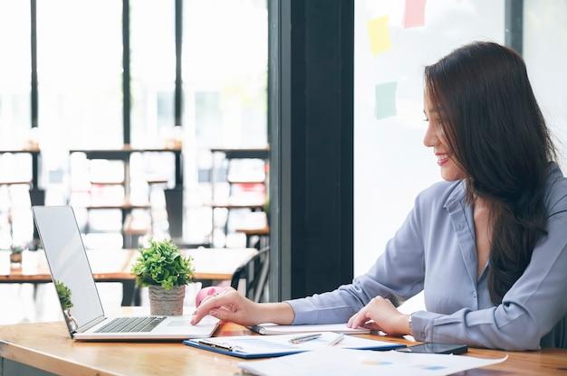 オフィスの机に座って、幸せでラップトップコンピューターで作業している魅力的な若い自信を持って実業家。