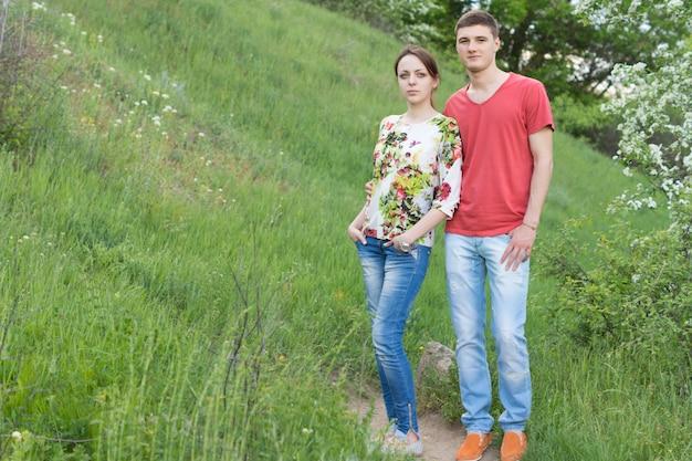 봄 꽃에 나무와 함께 잔디 언덕에 가깝게 서있는 자연 속에서 하루를 즐기는 매력적인 젊은 부부