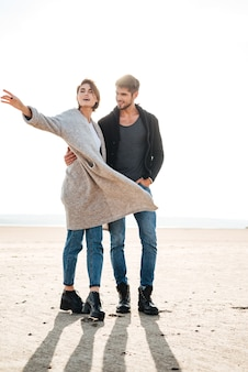 Attractive young couple having good time together at the beach in autumn