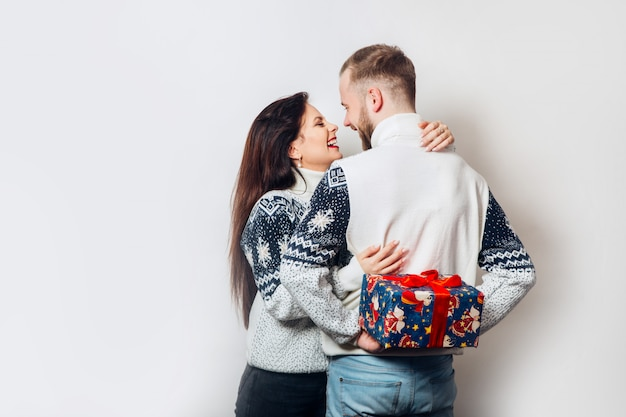 Attractive young couple holding gift over white