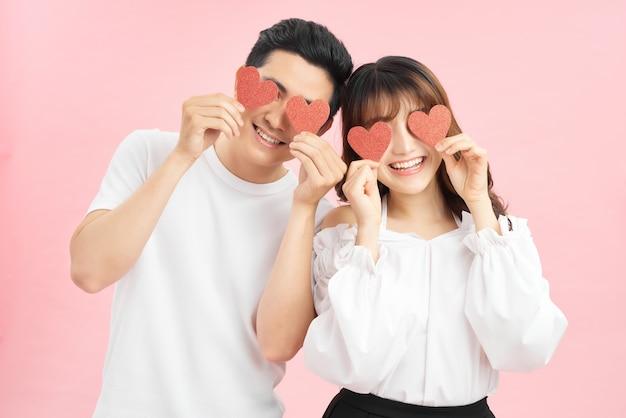 ピンクの背景で隔離の目の上に赤い愛の心を保持している魅力的な若いカップル