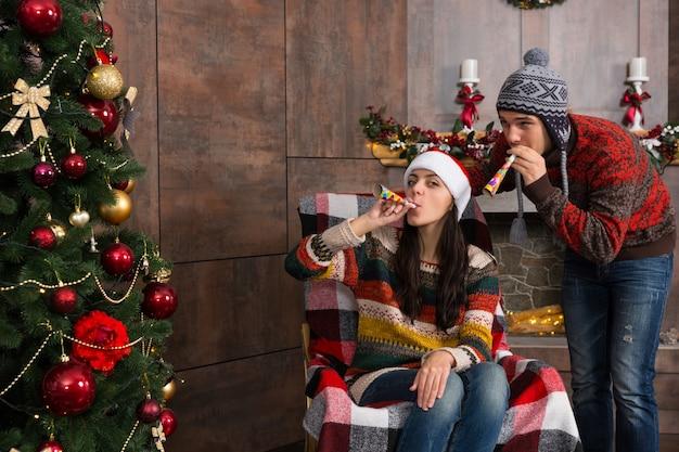 装飾された暖炉のあるリビングルームのロッキングチェアとクリスマスツリーの近くでパーティーの笛を吹く面白いクリスマスの帽子の魅力的な若いカップル