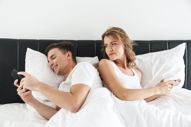 집에 있는 침실에 누워 있는 매력적인 젊은 부부, 화난 여자가 그를 보고 있는 동안 휴대전화를 사용하는 행복한 남자