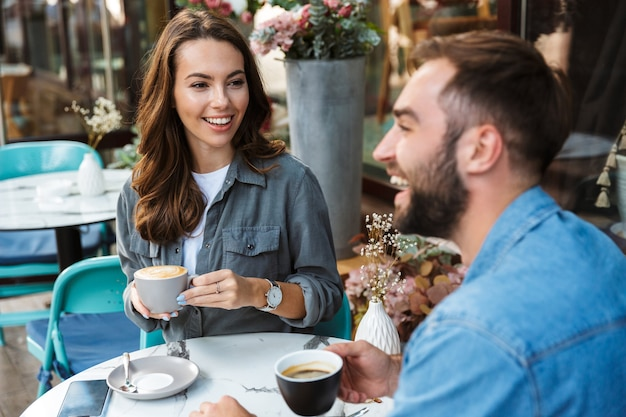 Attractive young couple in love having lunch while sitting at the cafe table outdoors, drinking coffee, talking