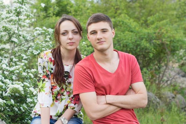 봄 날짜에 매력적인 젊은 부부는 나무 앞에서 가깝게 포즈
