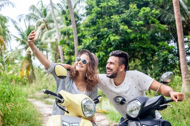 ジャングルの中でバイクの魅力的な若いカップルは、スマートフォンでselfieを作る