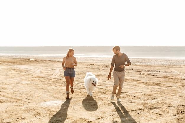 Привлекательная молодая пара играет со своей собакой на солнечном пляже
