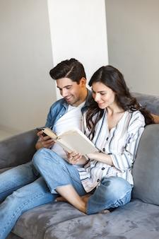 Привлекательная молодая пара отдыхает на диване у себя дома, читая бумажную книгу, используя мобильный телефон