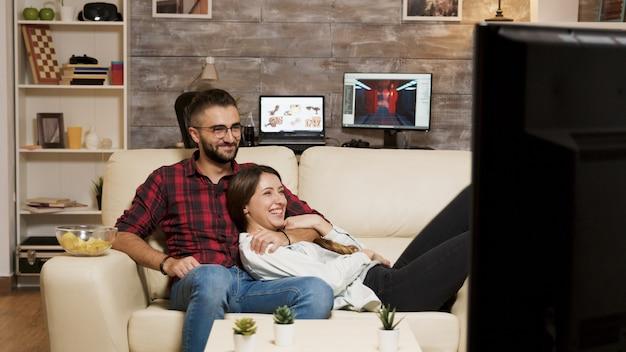 テレビで映画を見ながらソファでリラックスする魅力的な若いカップル。