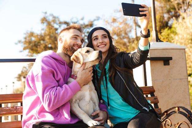 魅力的な若いカップルが犬と一緒にビーチのベンチに座って、自分撮りをしています