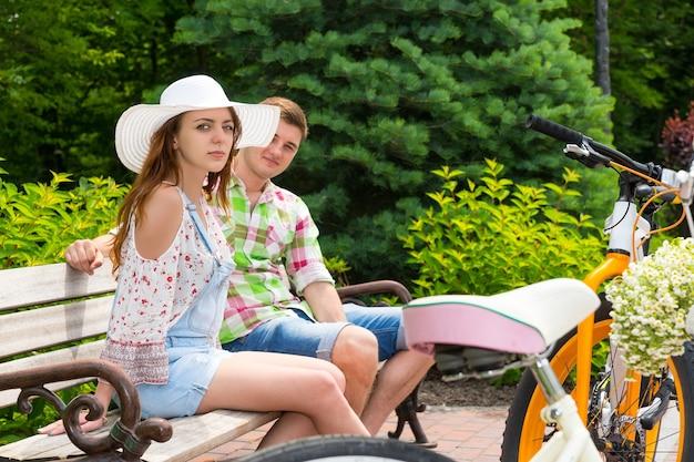 아름다운 녹색 공원의 벽돌 보도에 주차된 자전거 근처 벤치에 앉아 있는 매력적인 젊은 부부