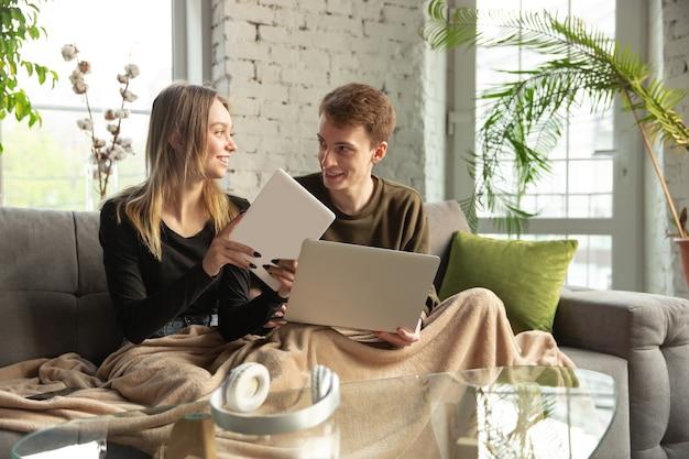 Привлекательная молодая пара, используя устройства вместе, планшет, ноутбук, смартфон, беспроводные наушники. связь, концепция гаджетов. технологии, соединяющие людей в самоизоляции. образ жизни дома.