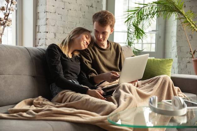 함께 장치, 태블릿, 노트북, 스마트 폰, 헤드폰 무선을 사용하는 매력적인 젊은 부부. 통신, 가제트 개념. 자기 절연으로 사람을 연결하는 기술. 집에서의 라이프 스타일.