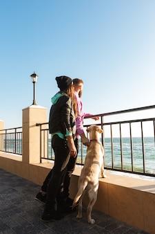 Привлекательная молодая пара гуляет на пляже со своей собакой
