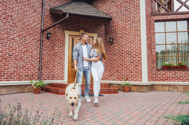 Привлекательная молодая пара с лабрадором перед их новым красивым домом