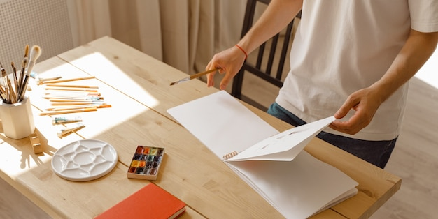 Attractive young creative man in a white t-shirt holding sketchbook and pencil in modern studio. colored pencils on a wooden table. concept diy. real art maker in action.