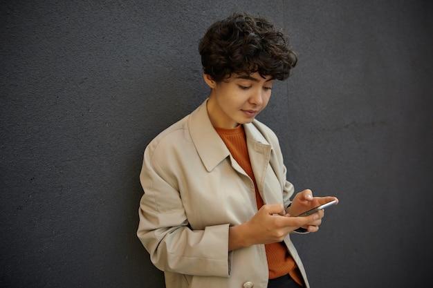 トレンディな服装で都市環境の上に立って、彼女の手で携帯電話を保持し、折りたたまれた唇で画面を見ている短いヘアカットの魅力的な若い巻き毛のブルネットの女性
