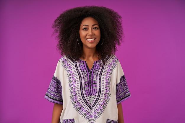 Attraente giovane donna riccia con pelle scura che indossa una camicia bianca fantasia, posa su viola con le mani verso il basso con un sorriso ampio e sincero