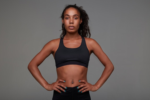 Привлекательная молодая кудрявая длинноволосая брюнетка с темной кожей, спокойно смотрящая стоя, одетая в спортивный черный топ