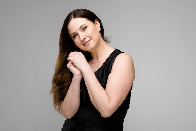 Attractive young cute positive brunette caucasian smiling business woman in black dress isolated on gray
