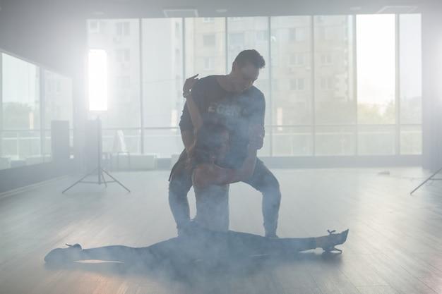 彼女のパートナーが彼女を助けている間、彼女の足を伸ばす魅力的な若いダンサー。しつこいダンサー。美しいポーズ。煙の中で踊る。