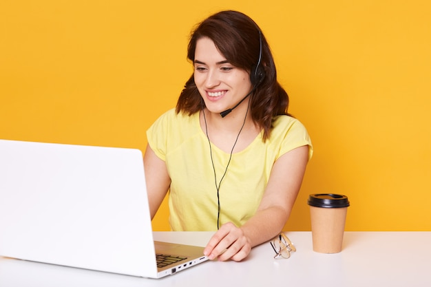 Attractive young dark haired woman with headset and microphone, working as operator online, wearing casual yellow t shirt