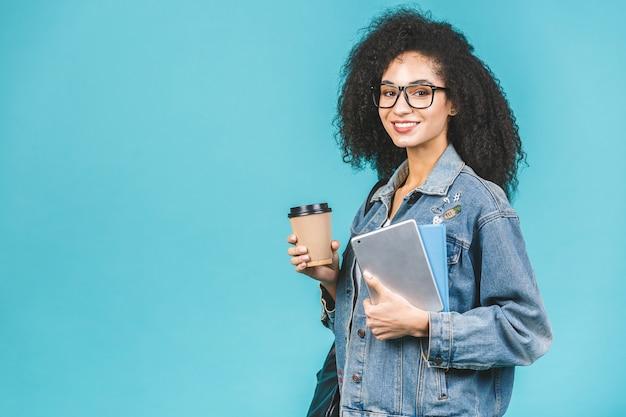 Привлекательная молодая темнокожая афроамериканская женщина, пьющая кофе и держащая книги и планшет. изолированные на синем фоне.
