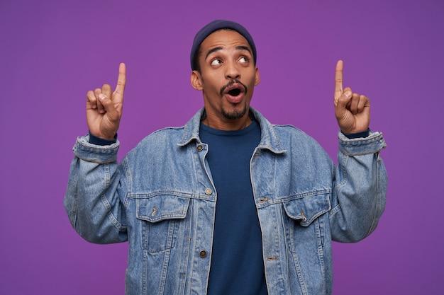 Привлекательный молодой темнокожий брюнет с бородой, держа указательные пальцы поднятыми, глядя вверх с возбужденным лицом, изолированно от фиолетовой стены