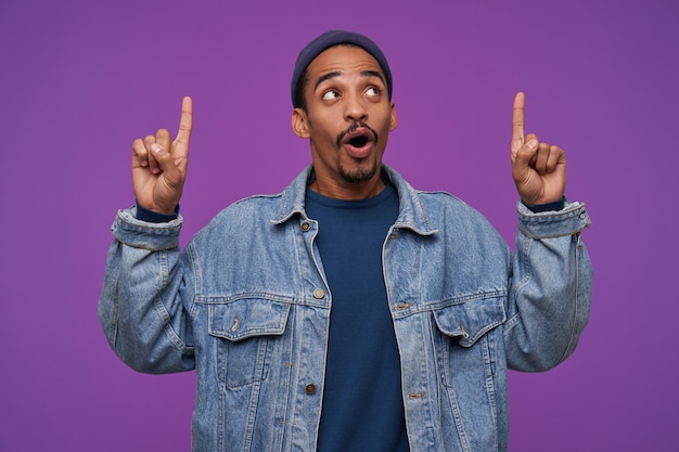 Attraente giovane maschio bruna dalla pelle scura con la barba che tiene gli indici sollevati mentre guarda verso l'alto con la faccia eccitata, isolato sopra il muro viola