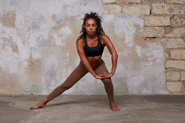 Attractive young dark skinned curly brunette female looking calmly with folded lips while making stretching exercises, dressed in athletic comfortable wear over brick wall
