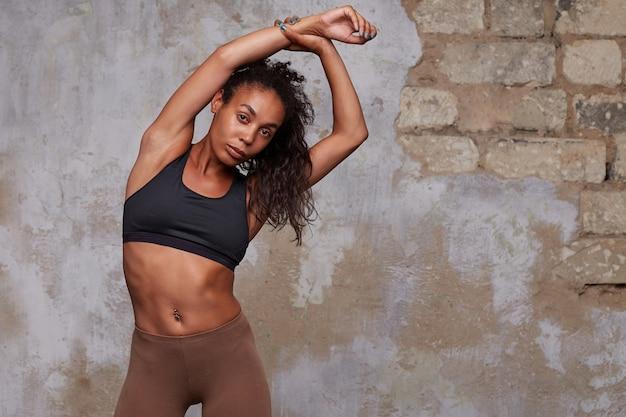 Attraente giovane donna bruna riccia dalla pelle scura con buon corpo alzando le mani sotto la testa mentre si allunga indietro prima di lezione di ballo, in posa sopra l'interno del soppalco
