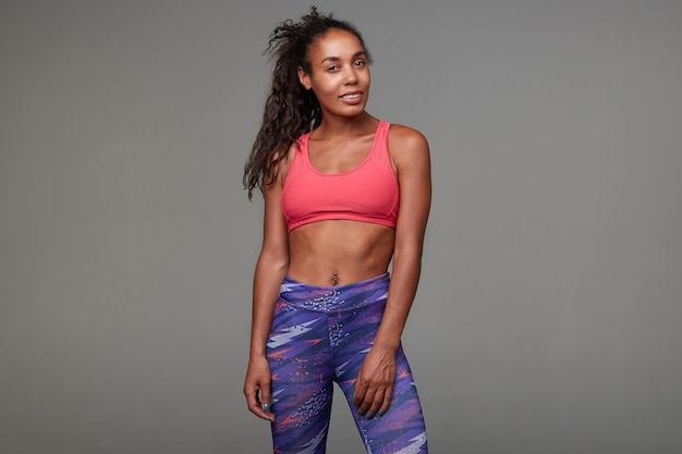Attractive young dark skinned curly brunette woman dressed in pink sporty top and printed leggins, looking positively with sincere smile, standing