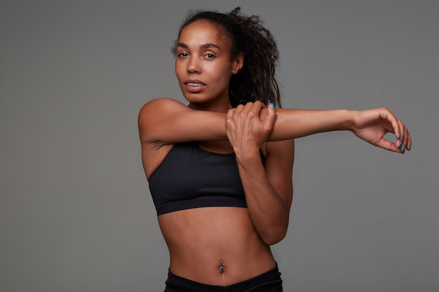 Attractive young dark skinned curly sportswoman with belly button piercing stretching her muscules after morning training in gym, posing in black top