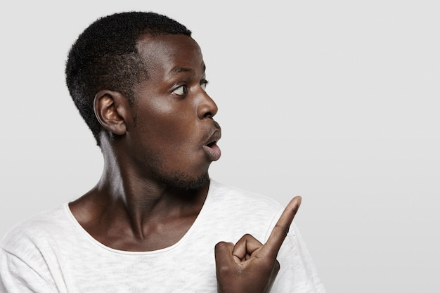Attractive young dark-skinned customer or employee looking surprised or shocked, pointing his finger at white wall with copy space for your advertising content, saying 'look at that!