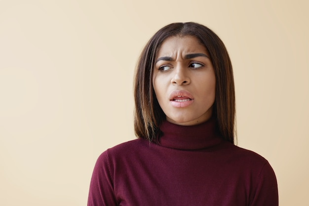 Attractive young dark skinned female employee with long straight hair looking sideways with irritated facial expression, annoyed with some disturbing noise while working at office