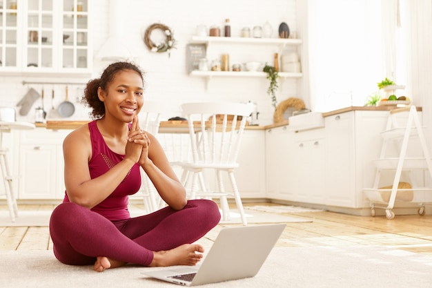 Attractive young dark skinned female fitness instructor working remotely on laptop, sitting on floor in stylish sportswear, writing article on healthy lifestyle. modern technology and sports concept