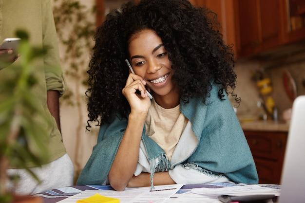 ラップのキッチンテーブルに座っているアフロのヘアカットと魅力的な若い浅黒い女性