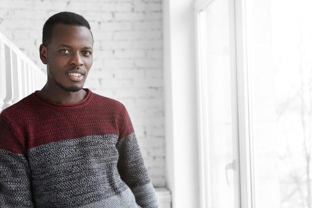 Привлекательный молодой темнокожий мужчина, одетый в свитер из джерси, имеет счастливый веселый вид