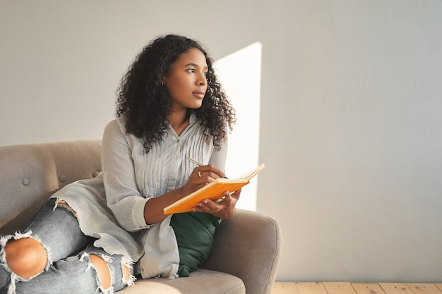 Attractive young dark skinned mulatto female with afro hairstyle relaxing on couch at home, having pensive thoughtful look, writing down ideas for her own startup project, using pen and copybook