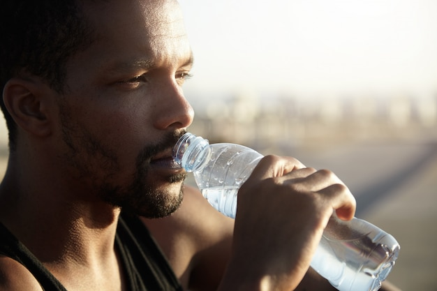 Attractive young dark skinned sportsman with short beard drinking water from bottle looking far away with thoughtful face expression, dressed in black sleeveless shirt, relaxing after morning run